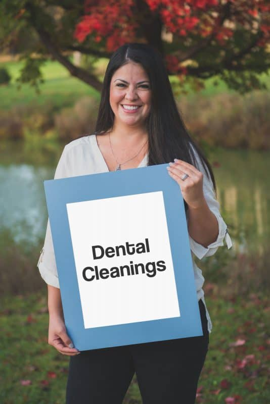 team member holding a sign saying dental cleanings