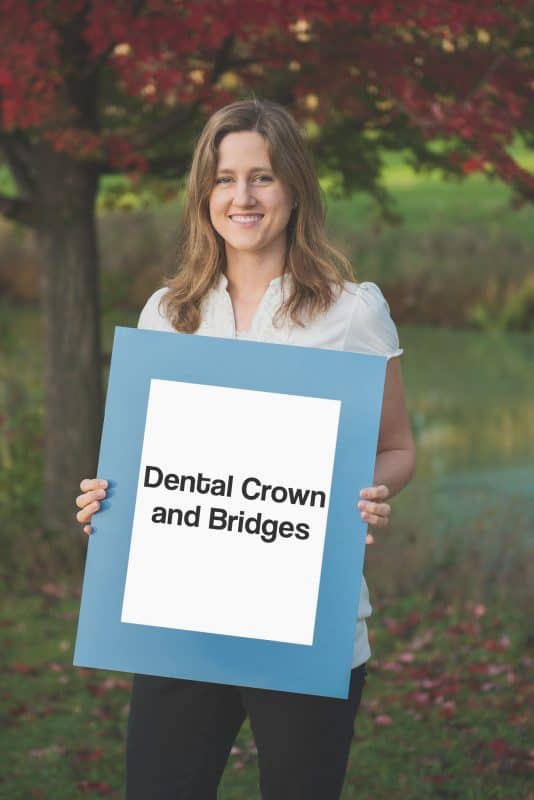 team member holding sign saying dental crown and bridges