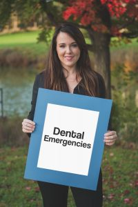 team member holding sign saying dental emergencies