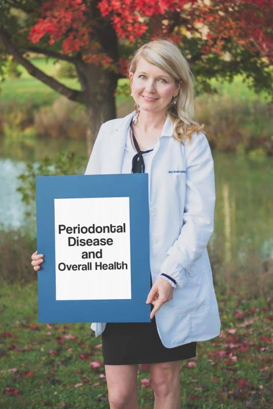kathryn alderman holding a sign saying periodontal disease and overall health
