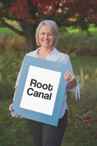 woman holding a Root Canal sign