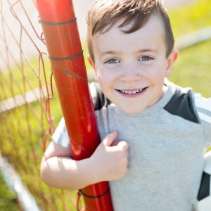 Image of young boy with a healthy smile who is getting ready to play soccer.